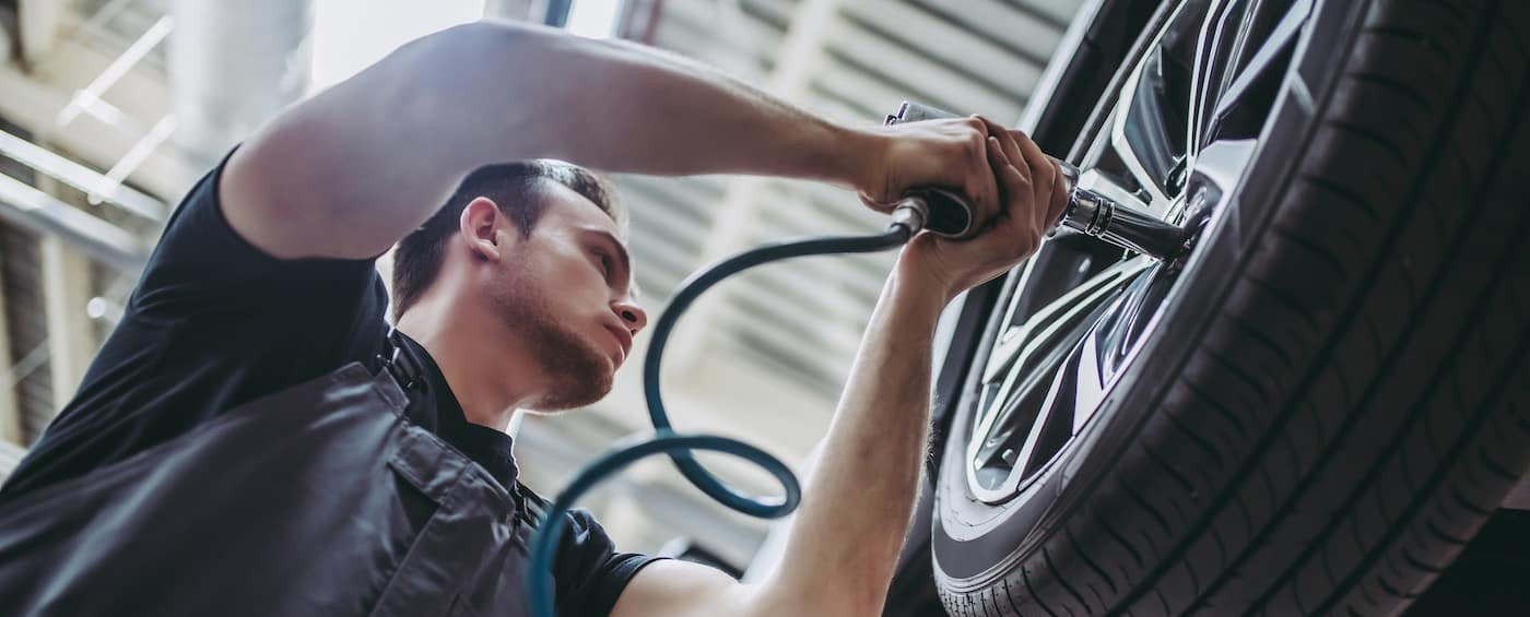 Handsome mechanic in uniform is working in auto service. Car repair and maintenance. Twisting/untwisting bolts on wheel.