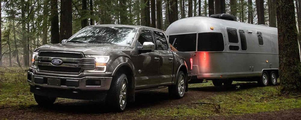 Silver Ford F-150 towing a trailer in the woods