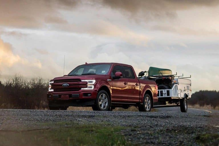 Maroon Ford F-150 towing a boat at dusk