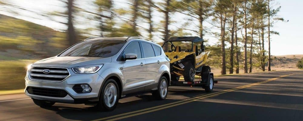 silver 2019 ford escape towing a yellow dune buggy on a forest highway