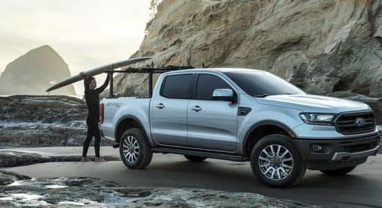 Ford Ranger Parked at Beach with Surfer Getting Board off Bed Rack