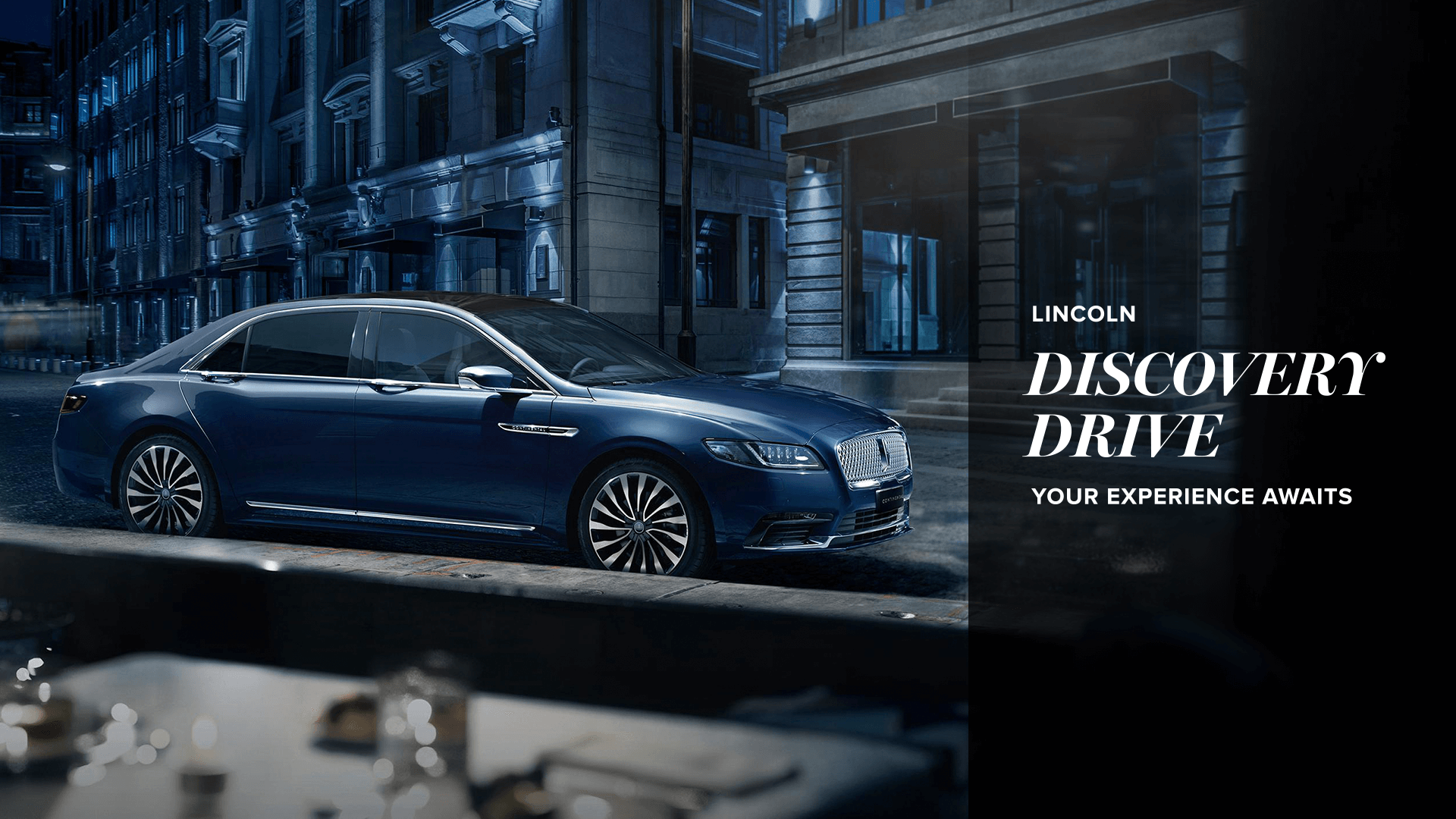Text: Lincoln Discovery Drive. Your experience awaits. Image: Photo of a blue Lincoln car parked on a roadside. View is from within a restaurant window. The set table is visible in the foreground. It's night time and the tone of the photo is very blue.