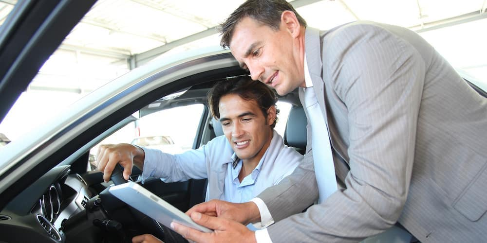 Car Dealer Going Over Paperwork with Car Buyer Cropped