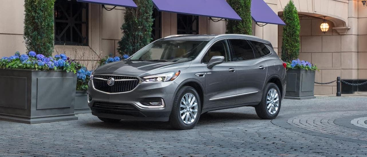 A gray 2020 Buick Enclave is parked in front of a tan stone building with purple awnings.