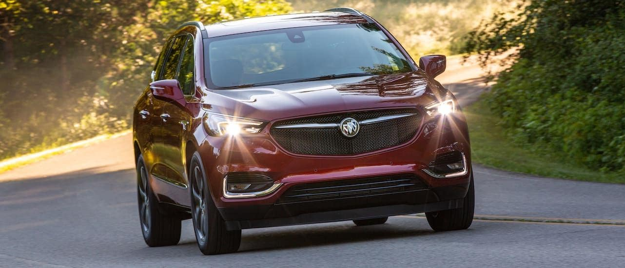 A red 2020 Buick Enclave is driving on a rural road near Lexington, KY, shown from the front.