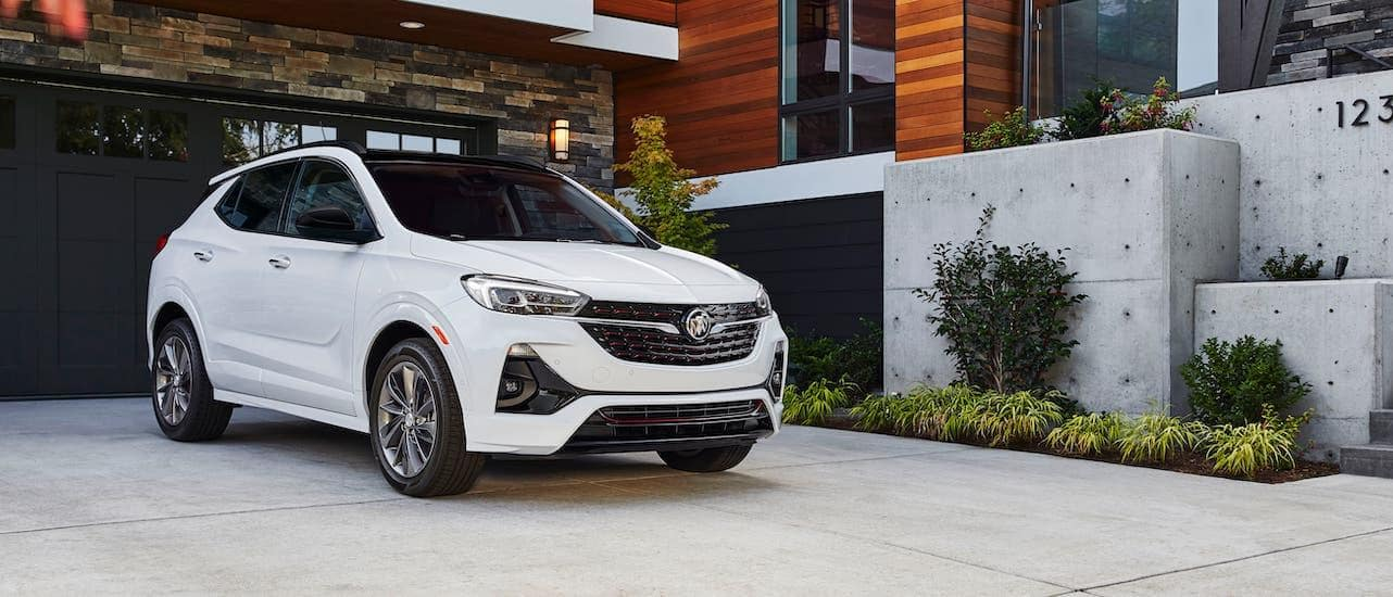 A white 2020 Buick Encore GX is parked in the driveway of a modern home.