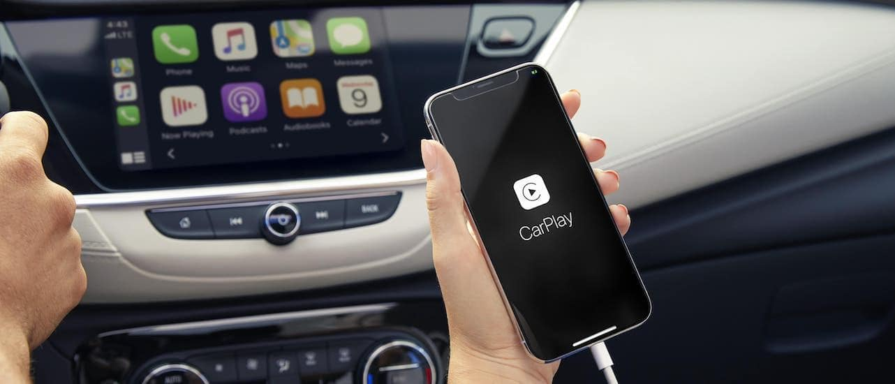 A hand is holding a cell phone while connecting to the infotainment screen in a 2020 Buick Encore GX.