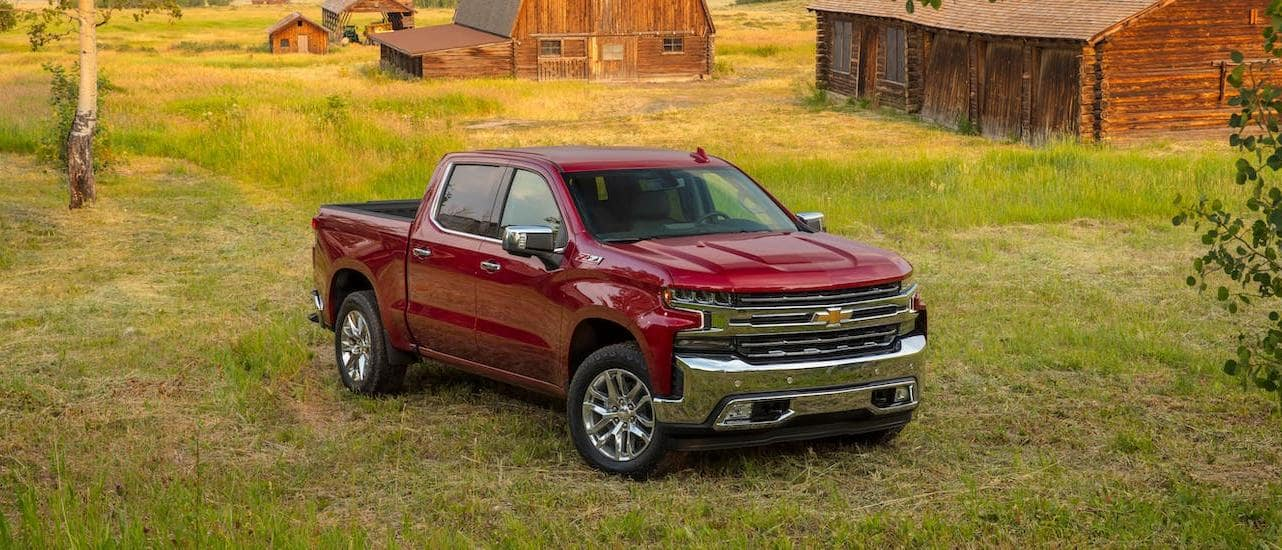 A red 2020 Chevy Silverado 1500 LTZ is parked in front of barns and mountains.