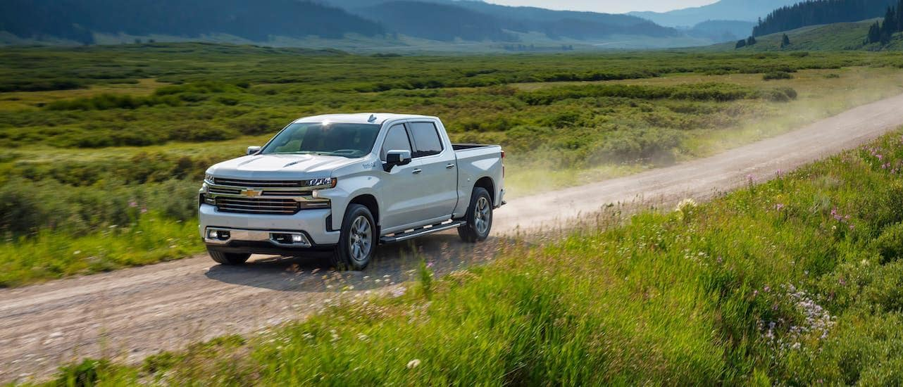 A white 2020 Chevy Silverado 1500 High Country is driving on a dirt road with mountains in the distance.