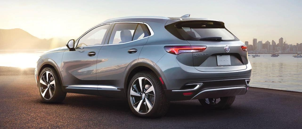 A gray 2021 Buick Envision is shown from the rear parked in front of a pier with a city in the distance.