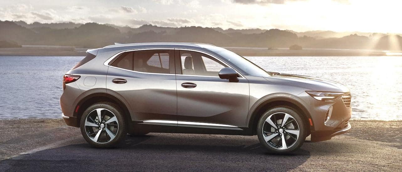 A gray 2021 Buick Envision is shown from the side in front of a beach at sunrise.