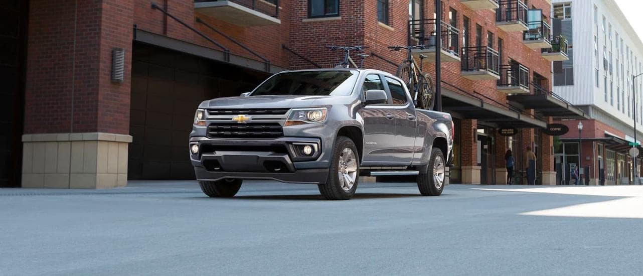 A gray 2021 Chevy Colorado LT with bikes in the bed is parked on a street near Lexington, KY.