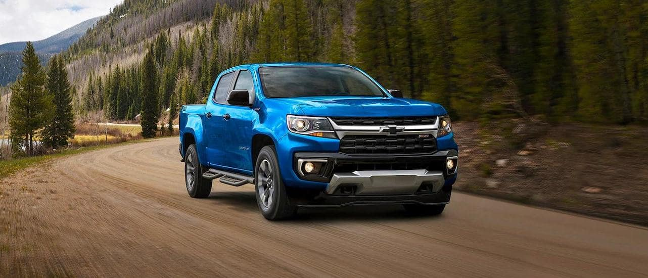 A blue 2021 Chevy Colorado Z72 is driving on a dirt road.