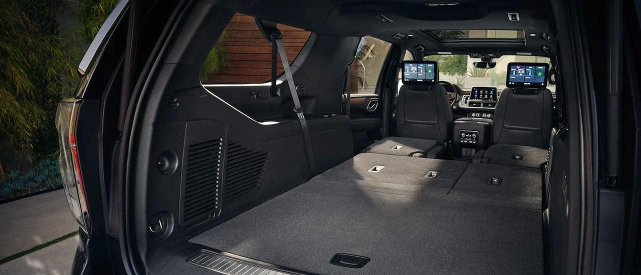 The cargo area of a 2021 Chevy Suburban is shown with the rear seats folded down.