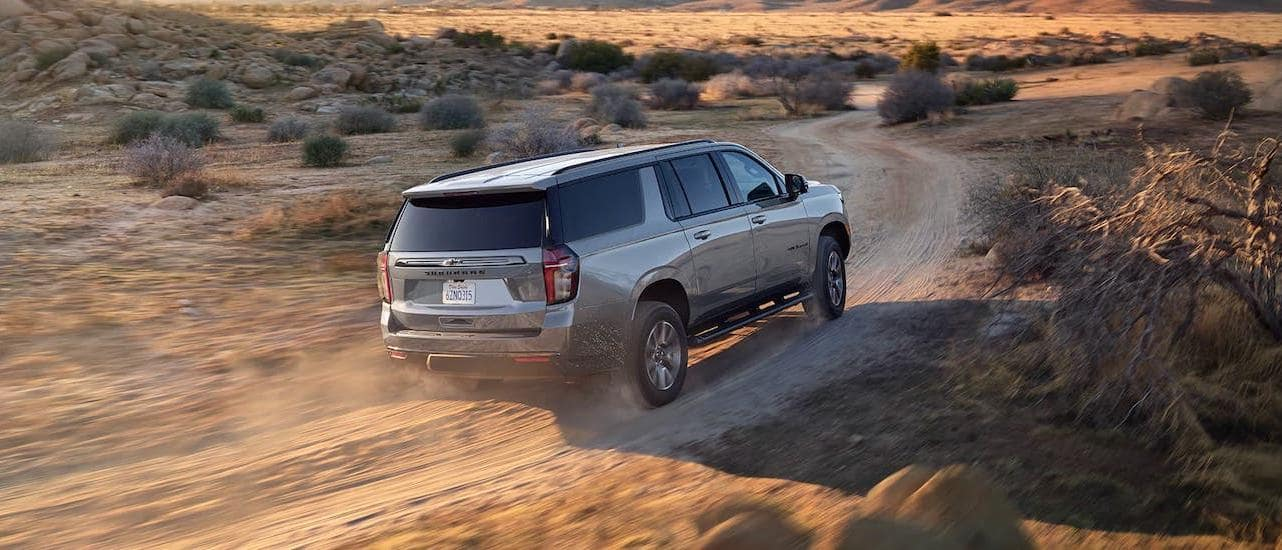 A gray 2021 Chevy Suburban is driving on a dirt road in the desert.