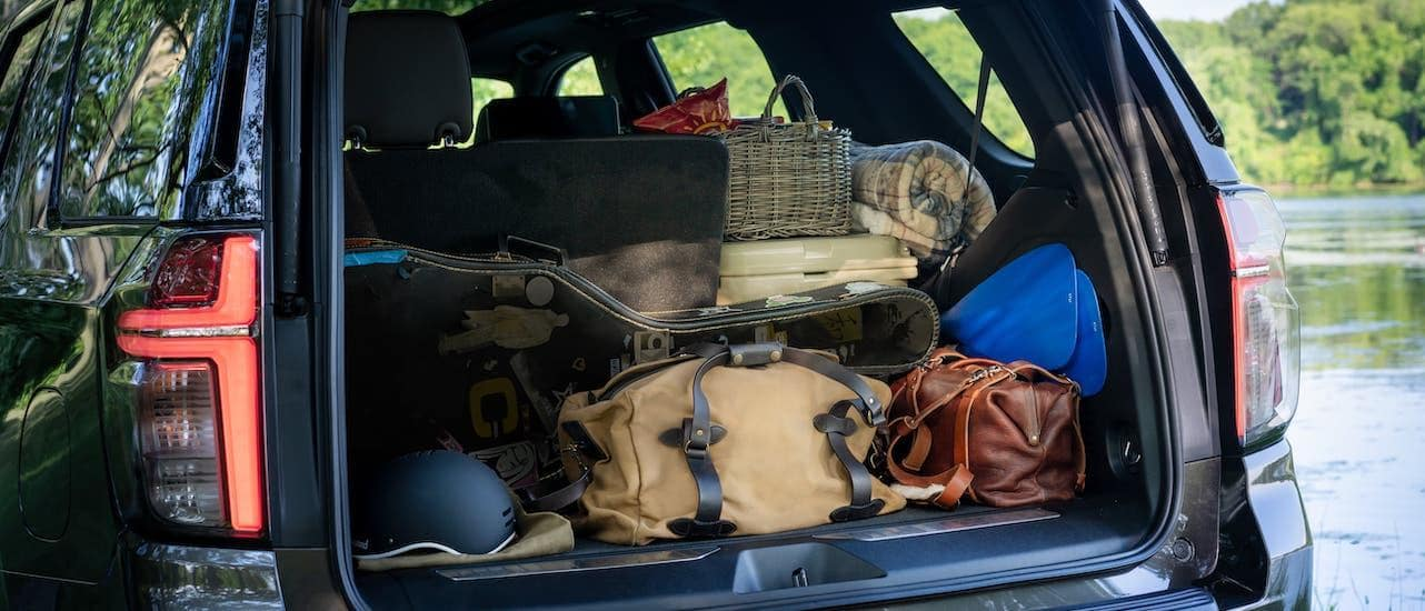 Luggage is shown in the cargo area of a black 2021 Chevy Tahoe that is parked in front of a pond.