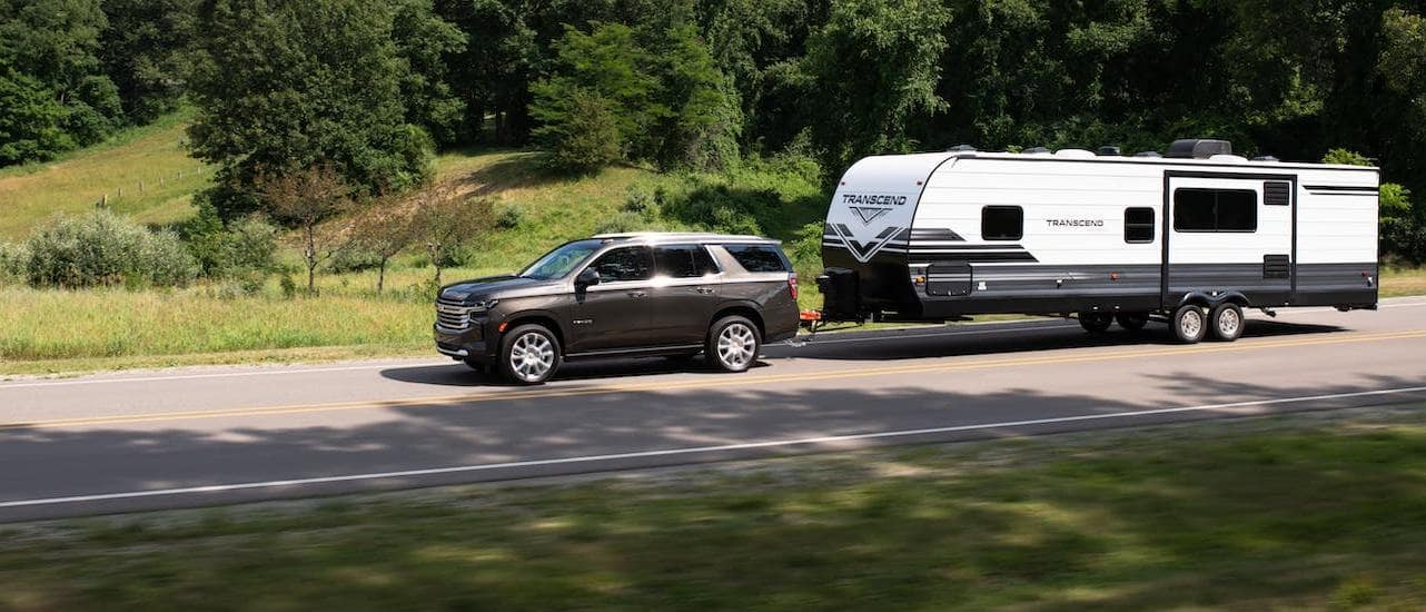 A gray 2021 Chevy Tahoe High Country is towing a camper on a highway near Lexington, KY.