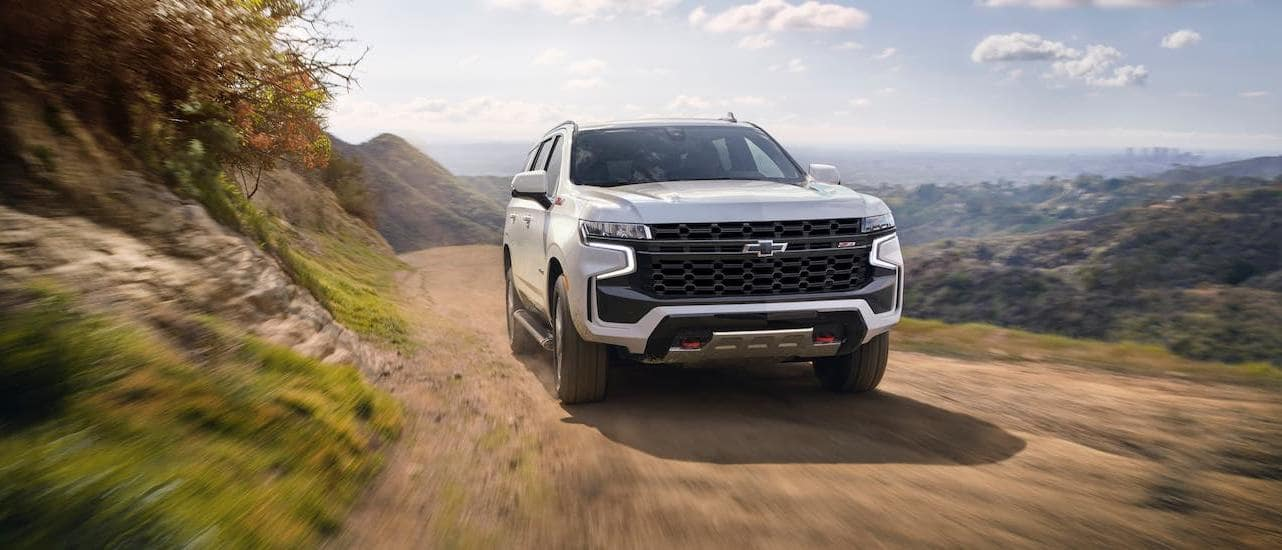 A white 2021 Chevy Tahoe Z71 is driving on a dirt road around a mountain and shown from the front.