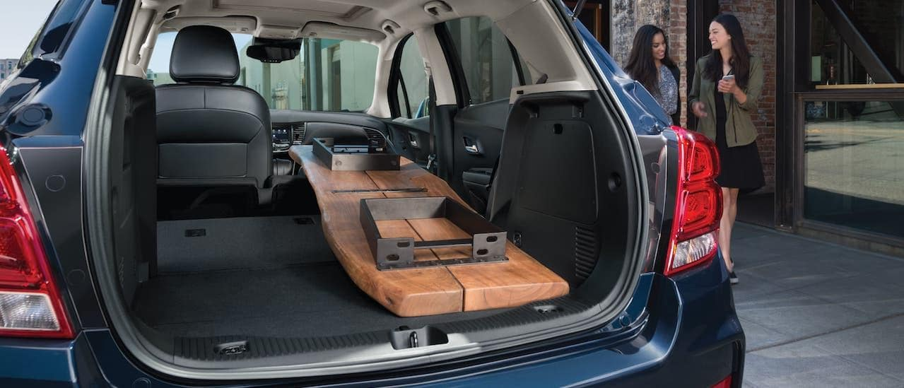 A table is shown in the cargo area of a blue 2021 Chevy Trax while women walk by.