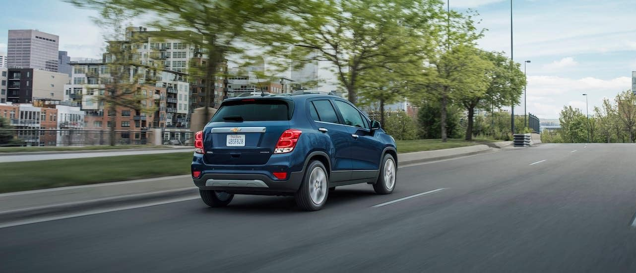 A blue 2021 Chevy Trax Premier is driving away on a highway near Lexington, KY.