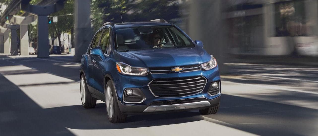 A blue 2021 Chevy Trax is shown from the front driving under a bridge near Lexington, KY.