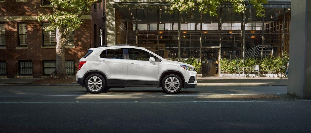 A white 2021 Chevy Trax is parked outside a cafe near Lexington and shown from the side.