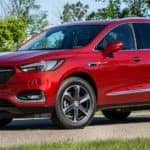 A red 2020 Buick Enclave with bikes on the rear is driving on a street near Lexington, KY.