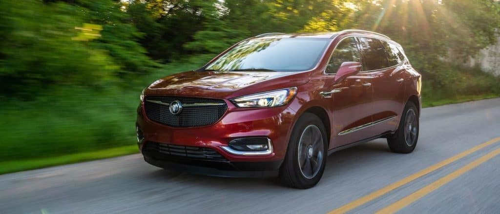 A red 2020 Buick Enclave Sport Touring from a local Buick dealer is driving on a rural road.
