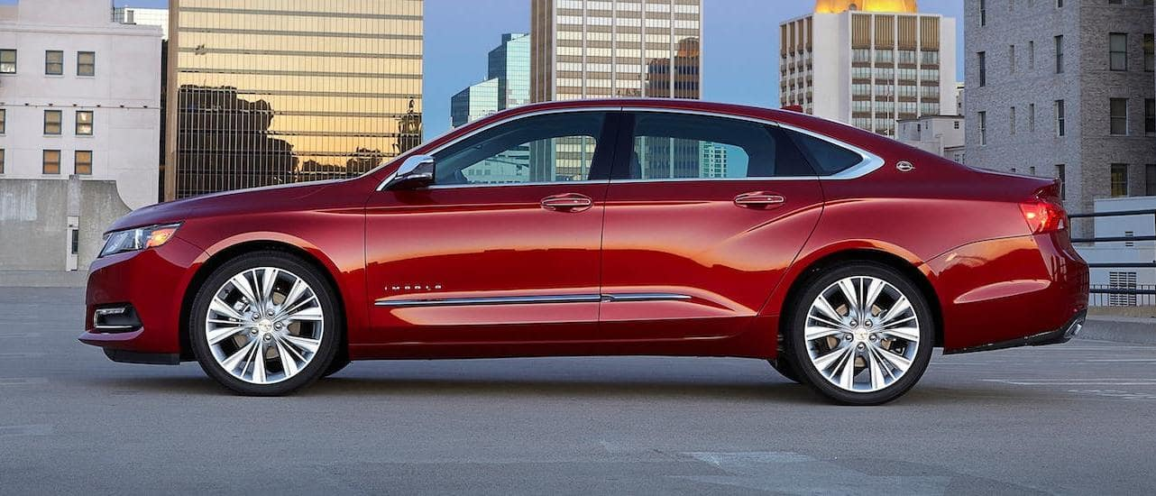 A red 2018 Chevy Impala from your local used car lot is shown from the side while parked atop a parking garage near Lexington, KY.