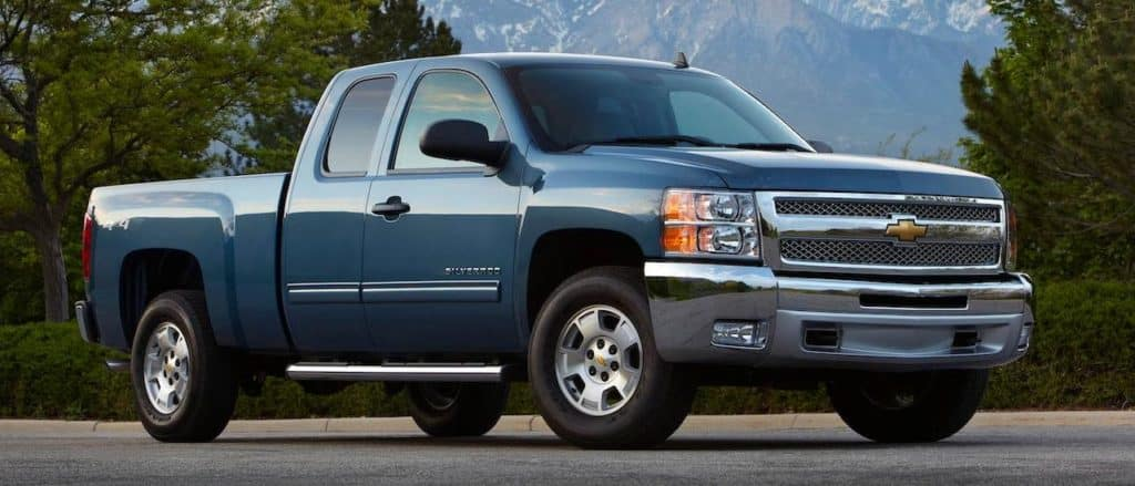 A popular used car near you, a blue 2013 Chevy Silverado LT, is parked in front of trees and mountains.