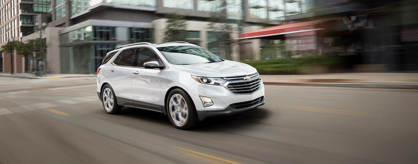 A white 2020 Chevy Equinox is driving on a city street.