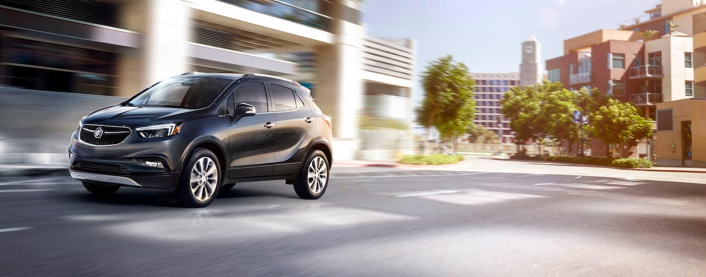 A black 2021 Buick Encore is driving on a city street.