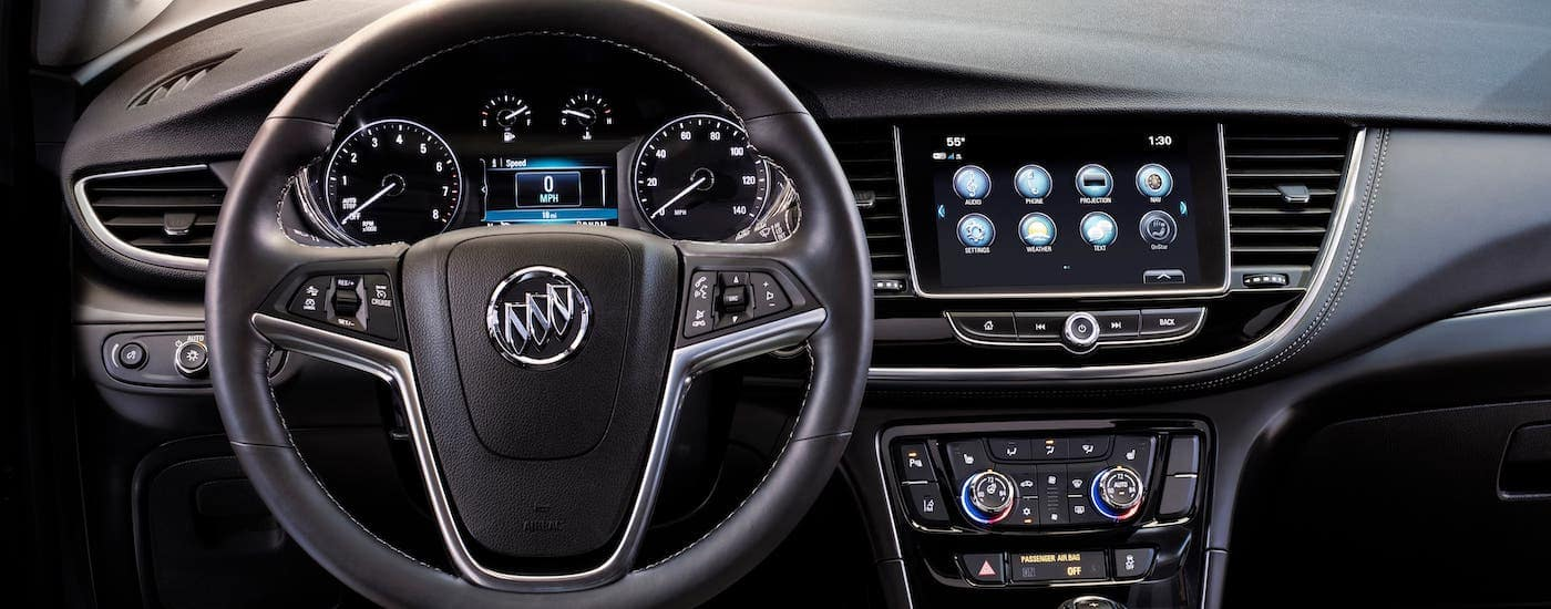 A closeup shows the steering wheel and infotainment screen in a 2021 Buick Encore.