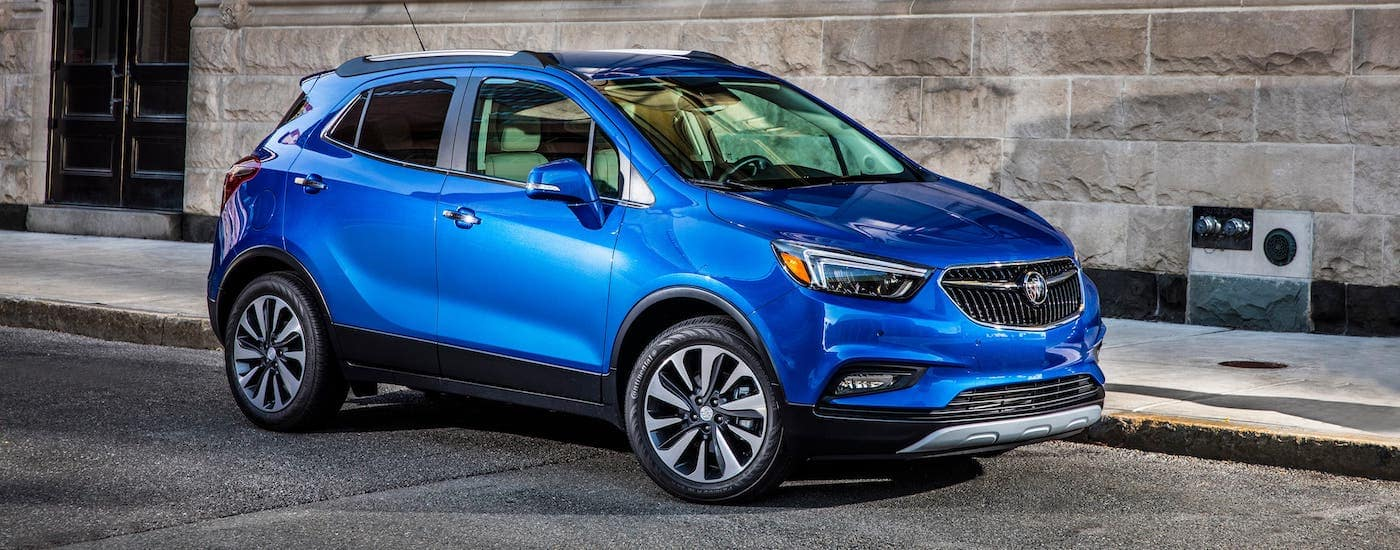 A blue 2021 Buick Encore is parked in front of a stone building.