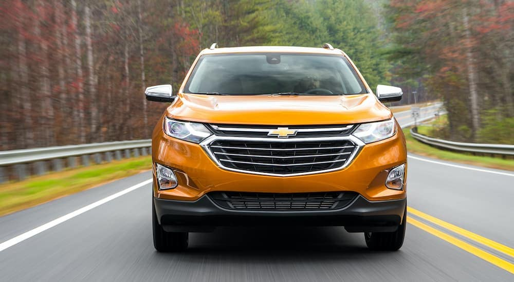 An orange 2017 Chevy Equinox is shown from the front driving down the highway.
