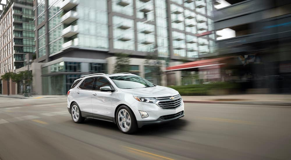 A white 2018 used Chevy Equinox is driving through the city.