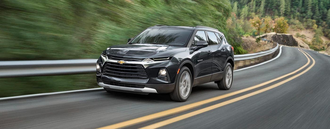 A black 2021 Chevy Blazer is driving on a winding road past trees.