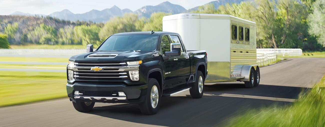A black 2021 Chevy Silverado 2500 is towing a white trailer past a field.