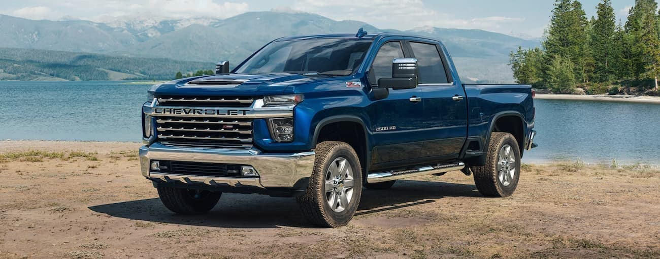 A blue 2021 Chevy Silverado 2500 is parked in front of a lake and mountains.