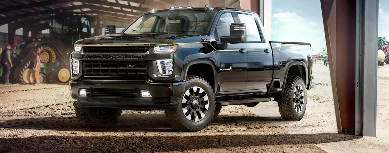 A black 2021 Chevy Silverado 2500 Carhartt Edition is parked in an open metal building on a farm.