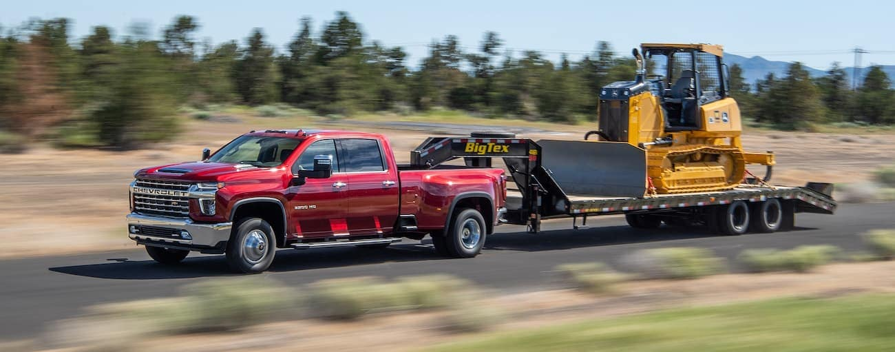 A red 2021 Chevy Silverado 3500 is towing heavy equipment past pine trees.