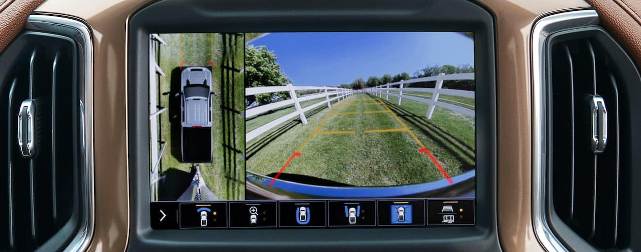 The infotainment screen in a 2021 Chevy Silverado 3500 is showing the trailer view while hooking up in a field.