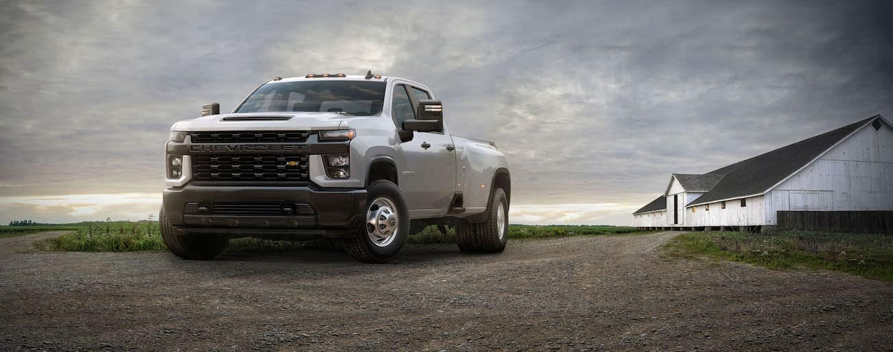 A white 2021 Chevy Silverado 3500 is parked in front of a white barn on a cloudy day.