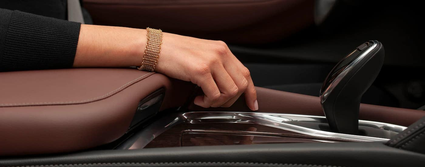 A close up is shown of the leather armrest and shifter on a 2021 Buick Enclave Avenir.