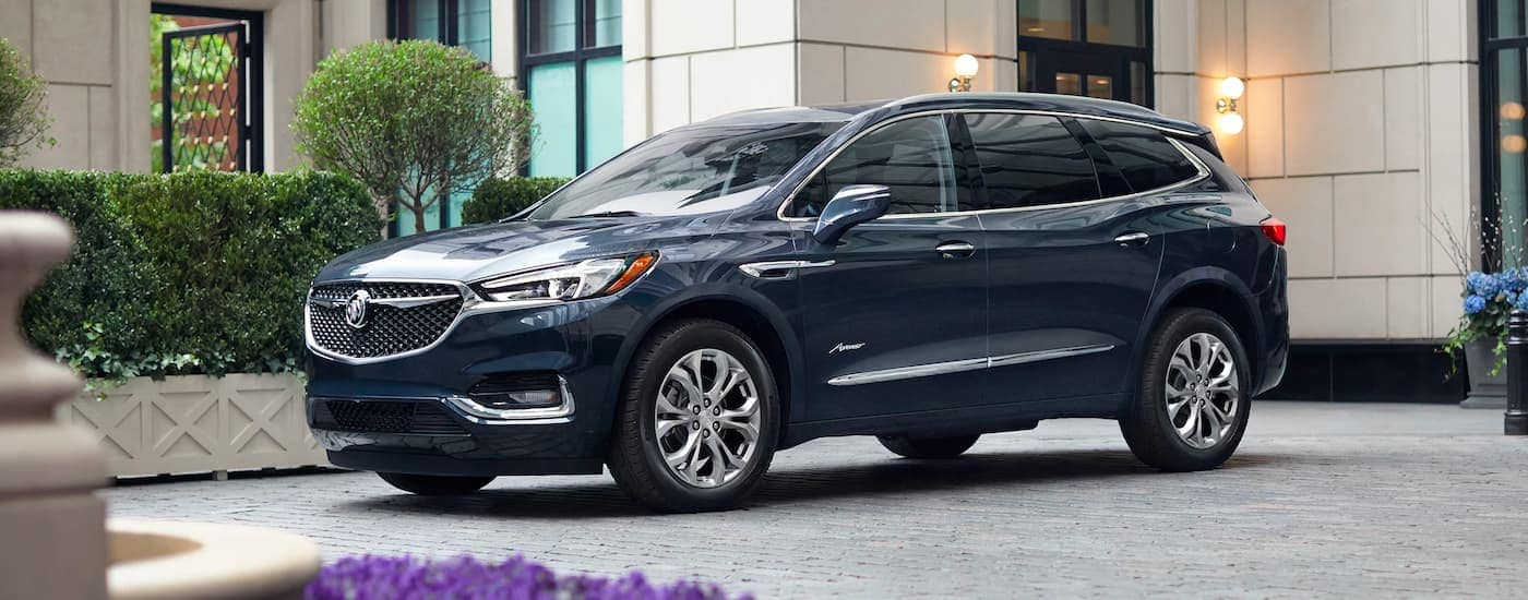A dark blue 2021 Buick Enclave Avenir is shown from the side parked in a courtyard.