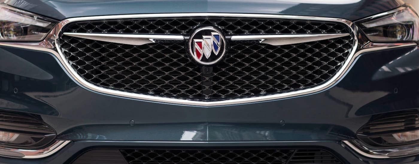 A close up is shown of the grille and headlights on a a dark blue 2021 Buick Enclave Avenir