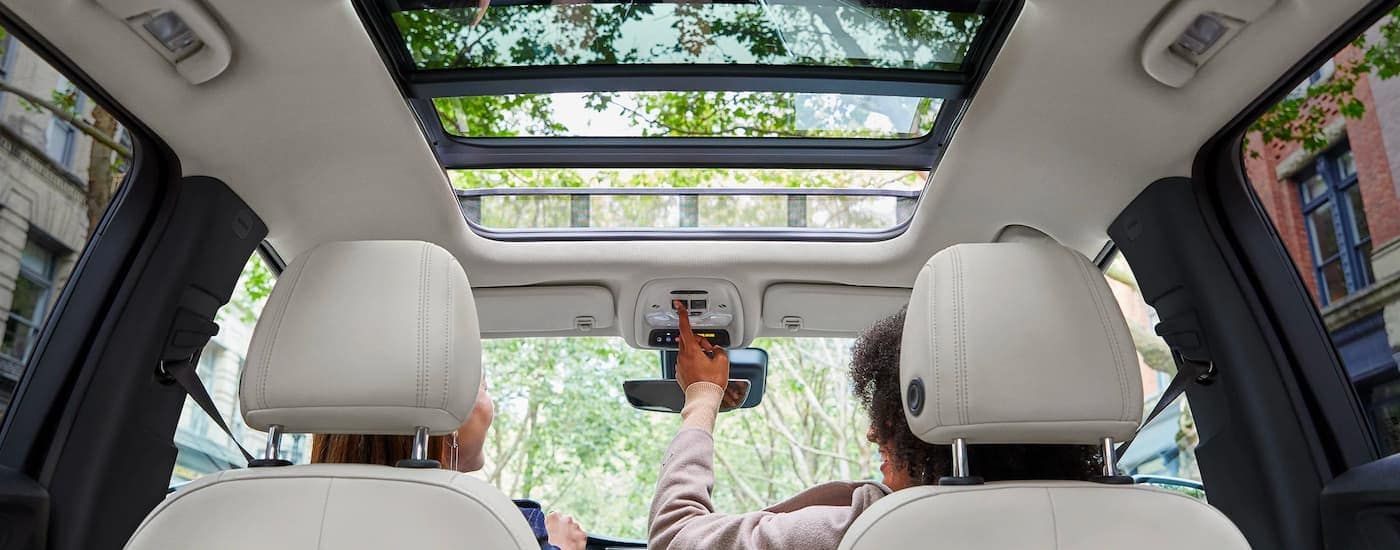 The sunroof and light grey interior are shown from a low angle on a 2021 Buick Encore GX.
