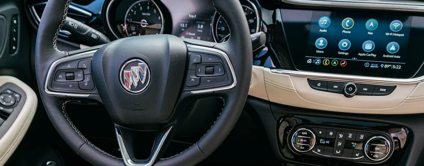 A close up shows the steering wheel and infotainment system on a 2021 Buick Encore GX.