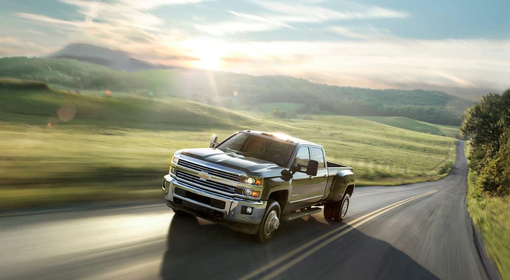 A black 2015 pre-owned Chevy 3500HD is speeding past a blurred field with the sun shining over a mountain.