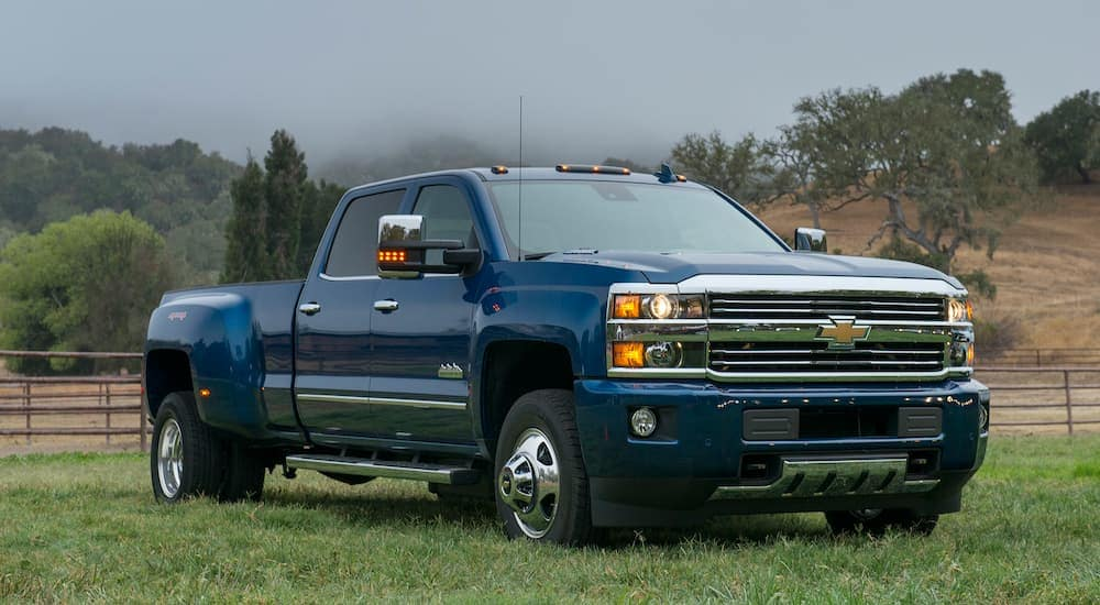 A blue 2016 Chevy Silverado 3500HD is parked in a field in front of a fence.